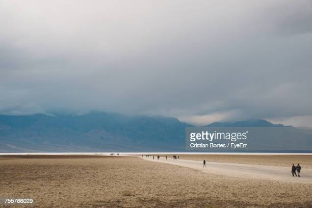 scenic view of arid landscape against cloudy sky - bortes stockfoto's en -beelden