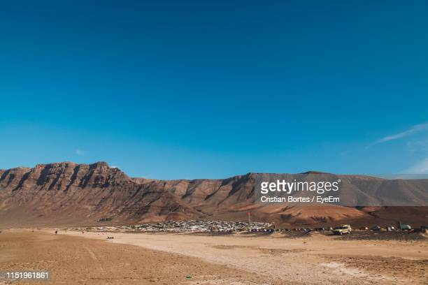 Scenic View Of Arid Landscape And Mountains Against Blue Sky