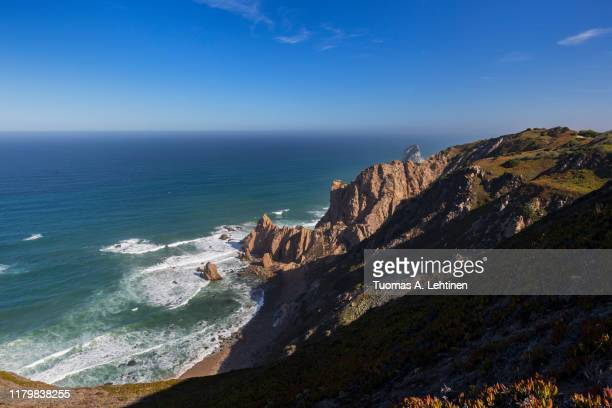 scenic view of atlantic ocean and rugged coast near cabo da roca, the westernmost point of mainland europe, in portugal. - rocky coastline stock pictures, royalty-free photos & images