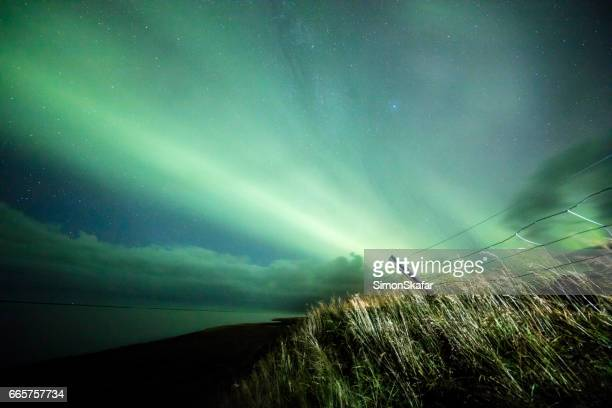 scenic view of aurora borealis over grassy field - elements stock photos and pictures