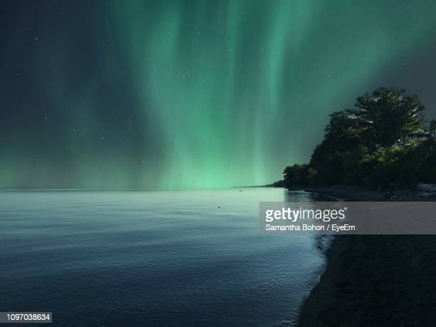 scenic view of aurora borealis over sea at night - us state border stock photos and pictures