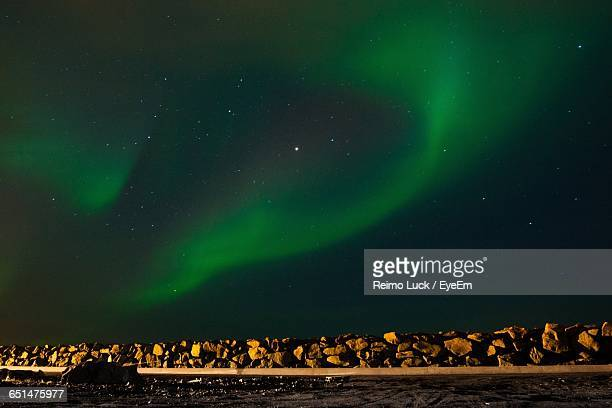 scenic view of aurora borealis over stones on field at night - northern norway stock pictures, royalty-free photos & images