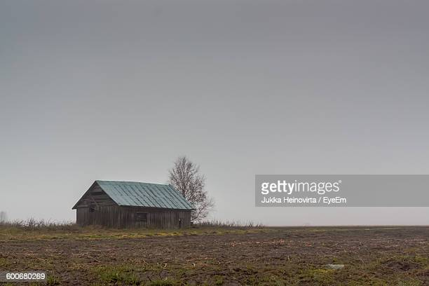 scenic view of barn on field against clear sky - heinovirta stock pictures, royalty-free photos & images