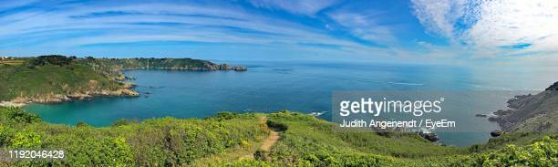 scenic view of bay against sky - isola di guernsey foto e immagini stock