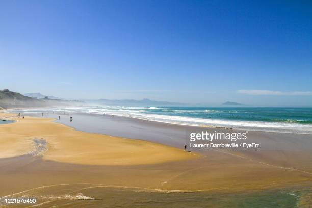 scenic view of beach against blue sky biarritz france - biarritz stock pictures, royalty-free photos & images