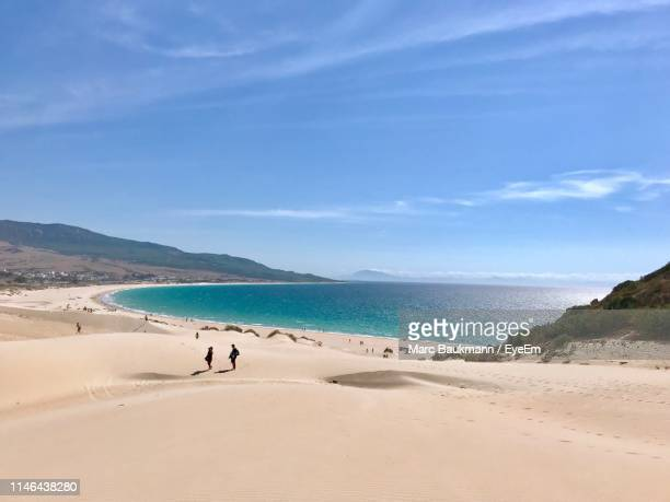 scenic view of beach against blue sky during sunny day - tarifa stock photos and pictures