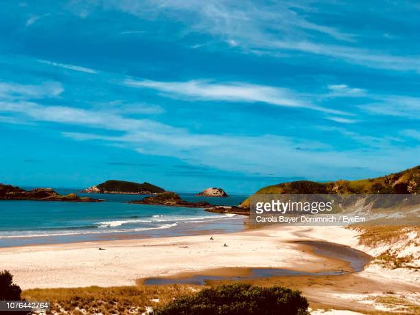 scenic view of beach against blue sky - whangarei heads stock-fotos und bilder