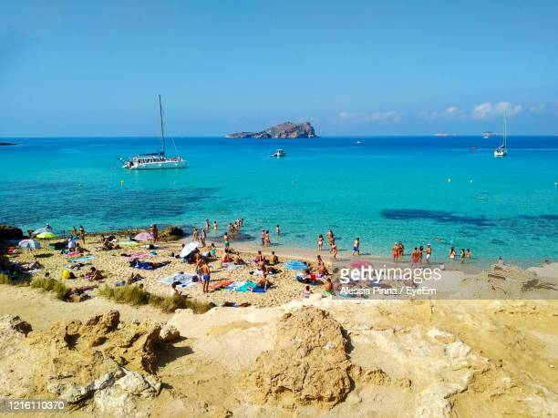 scenic view of beach against blue sky - beach sunbathing spain stock pictures, royalty-free photos & images