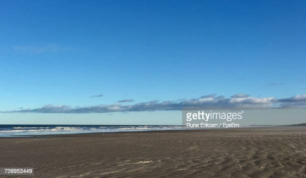 scenic view of beach against blue sky - eriksen foto e immagini stock