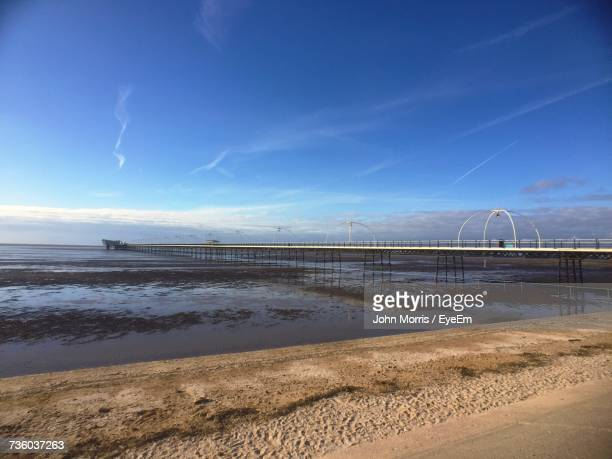 scenic view of beach against blue sky - southport england stock pictures, royalty-free photos & images