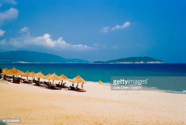 scenic view of beach against blue sky - hainan island stock pictures, royalty-free photos & images