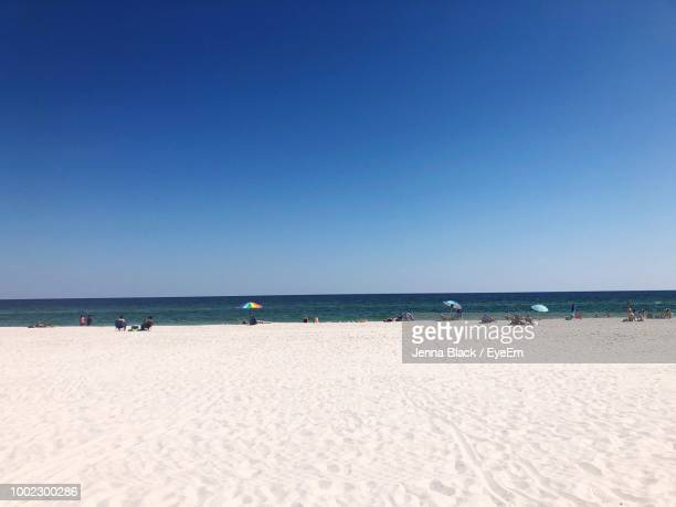 scenic view of beach against clear blue sky - gulf shores alabama stock pictures, royalty-free photos & images