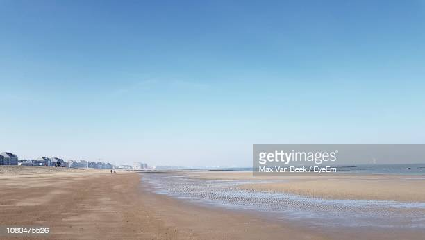 scenic view of beach against clear blue sky - coastline stock pictures, royalty-free photos & images