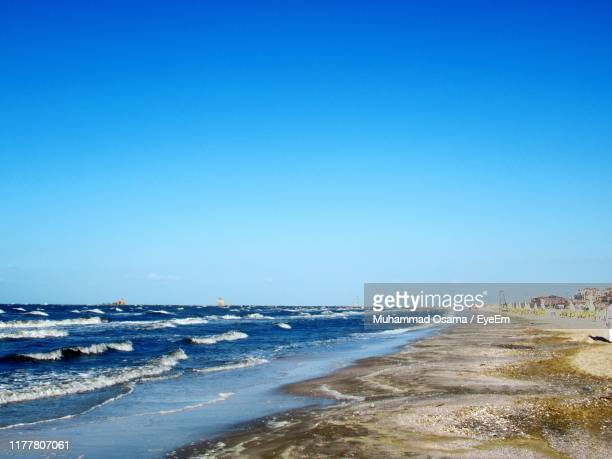 scenic view of beach against clear blue sky - port said stock pictures, royalty-free photos & images