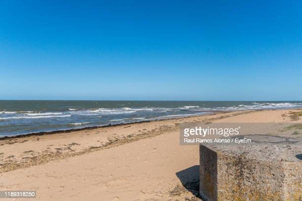 scenic view of beach against clear blue sky - juno beach normandy stock pictures, royalty-free photos & images