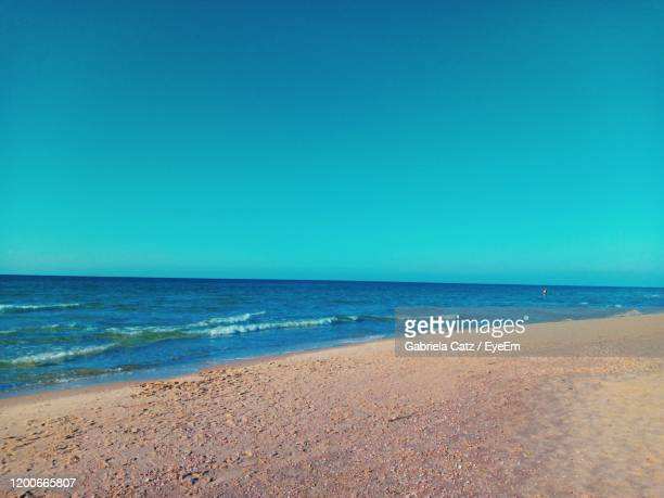 scenic view of beach against clear blue sky - clear sky stock pictures, royalty-free photos & images