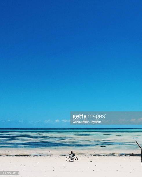 scenic view of beach against clear blue sky - zanzibar island stock photos and pictures