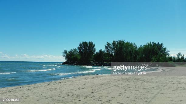 scenic view of beach against clear blue sky - lake ontario stock pictures, royalty-free photos & images