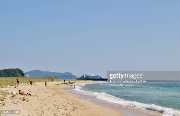 scenic view of beach against clear blue sky - anastasi foto e immagini stock
