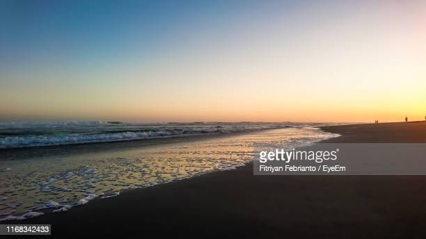 scenic view of beach against clear sky during sunset - ワイドショット ストックフォトと画像