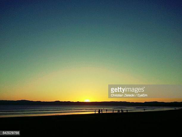scenic view of beach against clear sky during sunset - gisborne stock photos and pictures