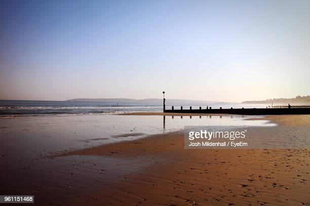 scenic view of beach against clear sky during sunset - bournemouth southampton stock pictures, royalty-free photos & images