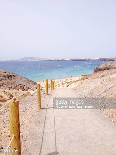 scenic view of beach against clear sky - puerto del carmen stock pictures, royalty-free photos & images