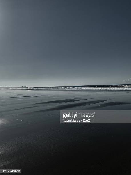 scenic view of beach against clear sky - naomi jarvis stock pictures, royalty-free photos & images