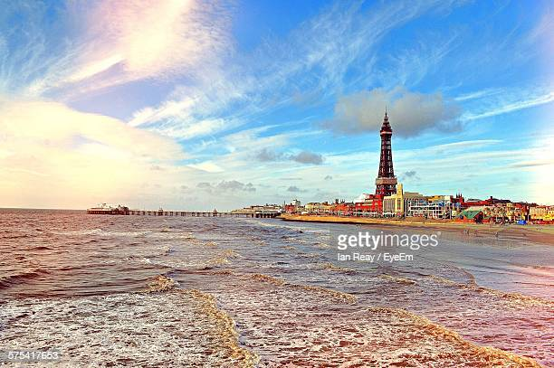 scenic view of beach against cloudy sky at sunset - blackpool stock photos and pictures