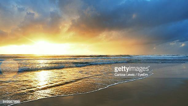 Scenic View Of Beach Against Cloudy Sky During Sunrise