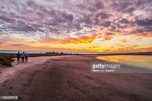 Scenic View Of Beach Against Cloudy Sky During Sunset
