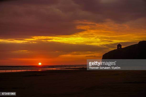 scenic view of beach against cloudy sky during sunset - castle rock colorado stock pictures, royalty-free photos & images