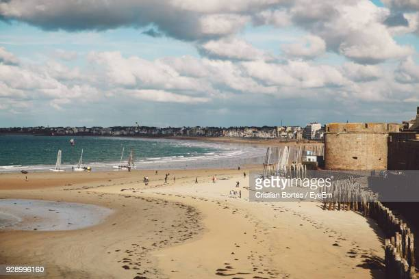 Scenic View Of Beach Against Cloudy Sky In City