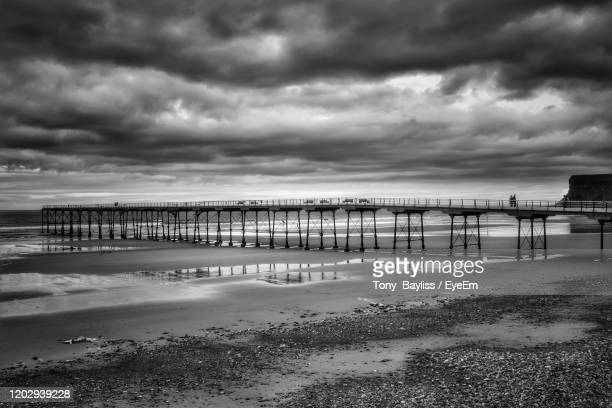 scenic view of beach against cloudy sky - saltburn stock pictures, royalty-free photos & images