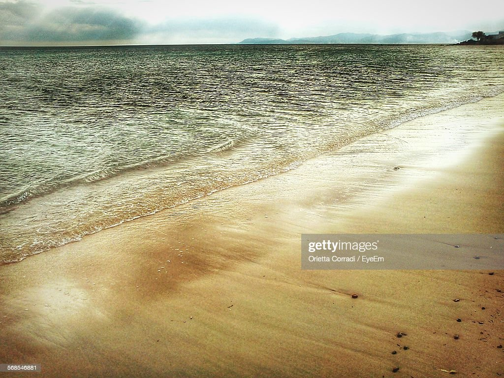 Scenic View Of Beach Against Cloudy Sky : Stock Photo