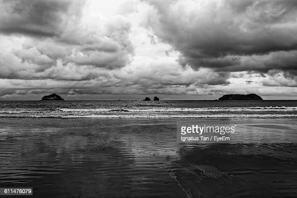 scenic view of beach against cloudy sky - ignatius tan stock photos and pictures