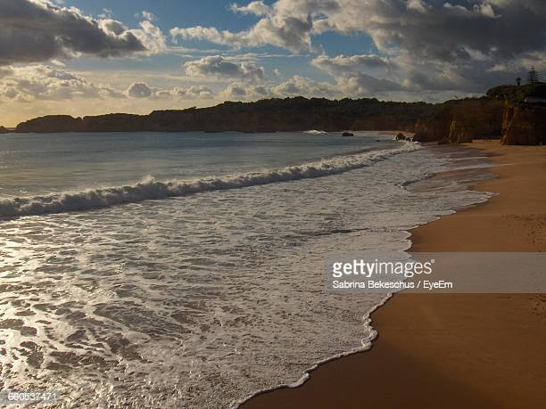 scenic view of beach against cloudy sky - alvor stock pictures, royalty-free photos & images