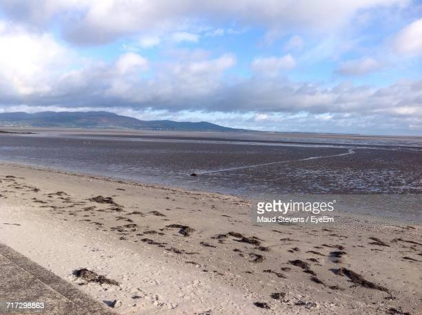 scenic view of beach against cloudy sky - blackrock stock pictures, royalty-free photos & images