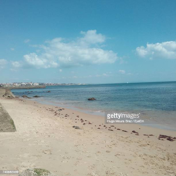 scenic view of beach against cloudy sky - moura stock photos and pictures