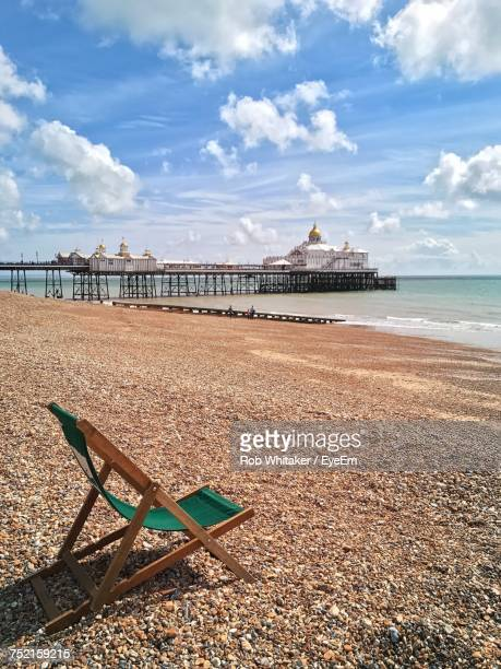 scenic view of beach against cloudy sky - eastbourne stock photos and pictures