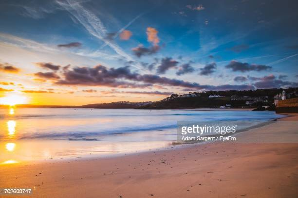 scenic view of beach against dramatic sky - penzance stock pictures, royalty-free photos & images