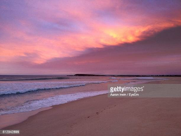 Scenic view of beach against orange sky