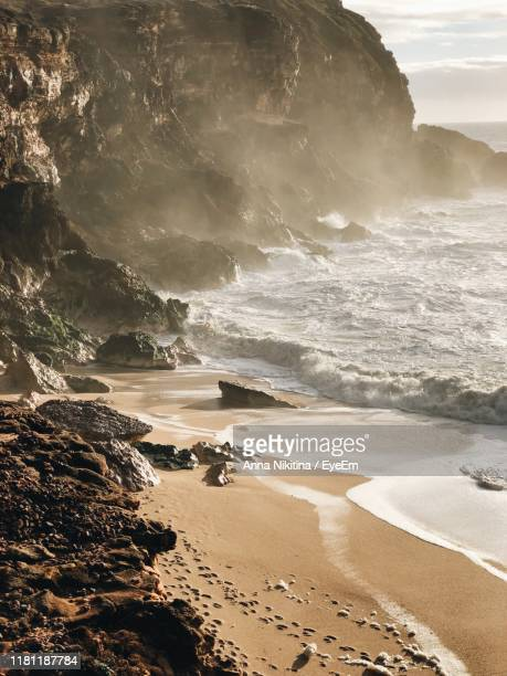 scenic view of beach against rock formations - nikitina stock pictures, royalty-free photos & images