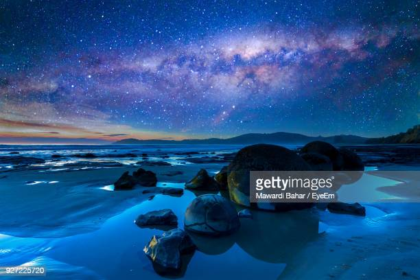 scenic view of beach against sky at night - hot spring stock pictures, royalty-free photos & images