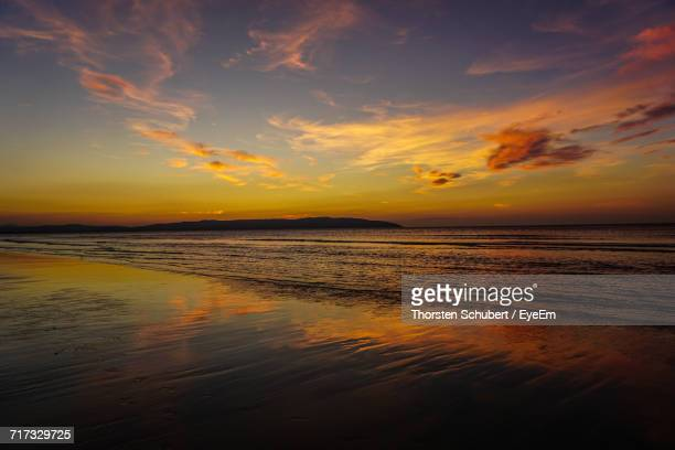 scenic view of beach against sky at sunset - castle rock colorado stock pictures, royalty-free photos & images