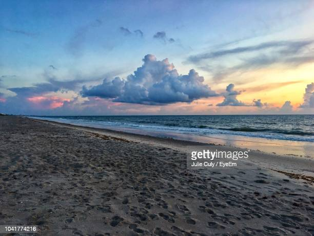 scenic view of beach against sky during sunset - julie culy stock pictures, royalty-free photos & images
