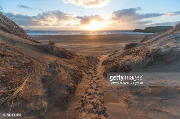 scenic view of beach against sky during sunset - south wales stock pictures, royalty-free photos & images