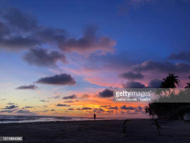 scenic view of beach against sky during sunset - côte d'ivoire stock pictures, royalty-free photos & images