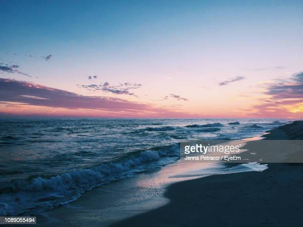 scenic view of beach against sky during sunset - gulf shores alabama stock pictures, royalty-free photos & images