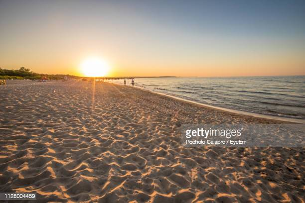 scenic view of beach against sky during sunset - gdansk stock pictures, royalty-free photos & images